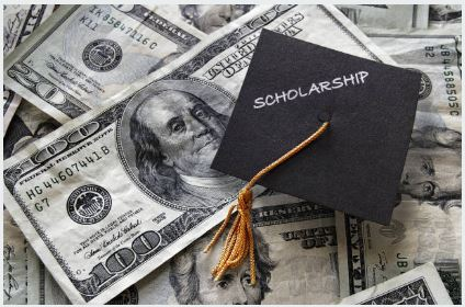 Image of graduation hat with Scholarship written on it sitting on top of hundred dollar bills