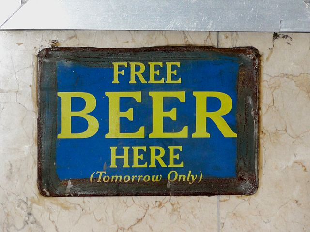 """A sign saying """"free beer here (tomorrow)"""""""