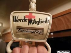 """Die Haltegriffe sind kreativ gestaltet: Mit doppelseitiger Werbung für das Rote Kreuz. Bei jedem mal herunterziehen des Griffes (von der """"Decke""""), rollt die Rolle im Inneren jeweils eine Position weiter."""