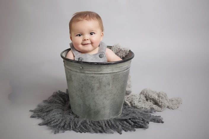 baby sitting in bucket
