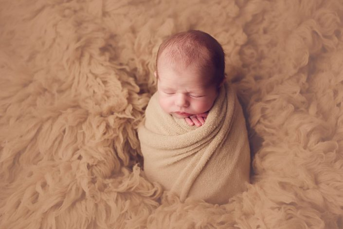 baby wrapped in beige on brown fur blanket