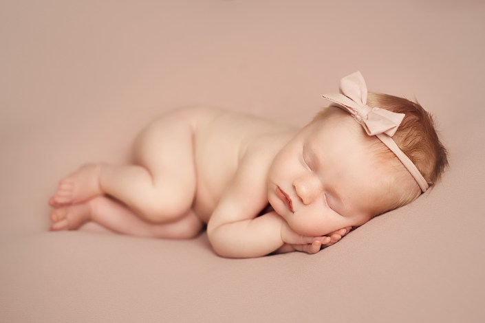baby girl on pink backdrop