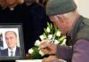 Ein älterer Bosnier schreibt vor dem Bild von Alija Izzetbegovic - cihan