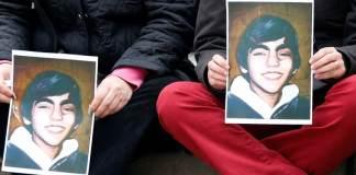 Berkin Elvans Fotos werden von zwei Personen hochgehalten.