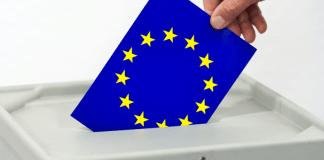 Ein Mann steckt am 20.02.2014 in in Frankfurt (Oder,Brandenburg) eine Europafahne in den Schlitz einer Wahlurne.