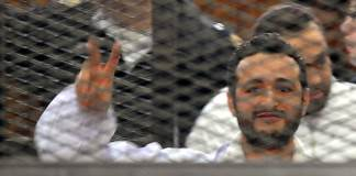 A file photo dated 22 December 2013 shows Egyptian activist Ahmed Douma flashing victory sign behind dock bars during his trial in Cairo, Egypt.