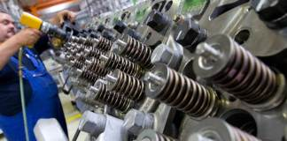 Ein Mitarbeiter montiert am 15.07.2011 einen Zylinderkopf an einem Dieselmotor in Magdeburg (Sachsen-Anhalt).