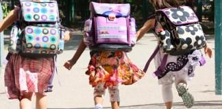 Drei Schulmädchen rennen gemeinsam zum Schultor.