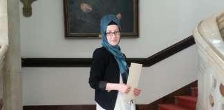 Die Bremerin Hüdanur Bayraktaroğlu steht mit ihrem Abitur-Zeugnis vor der Kamera.