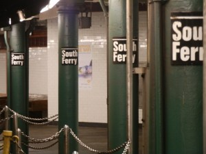 Station identification signs are mounted on cast-iron columns that line the platform.
