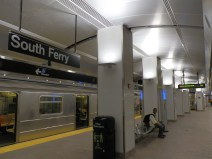 The central section of the platform, showing the station sign, central columns, and ceiling vault. The upward-shining, sconce-style light fixtures on the columns are of a different style than they were before Sandy. This is one of the few changes to the station that resulted from the restoration and repair work that took place between 2012 and 2017.