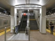 A stairway and escalator lead from the platform to a mezzanine at the northern end of the station.