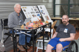 Old man and man in wheelchair with origami paper objects