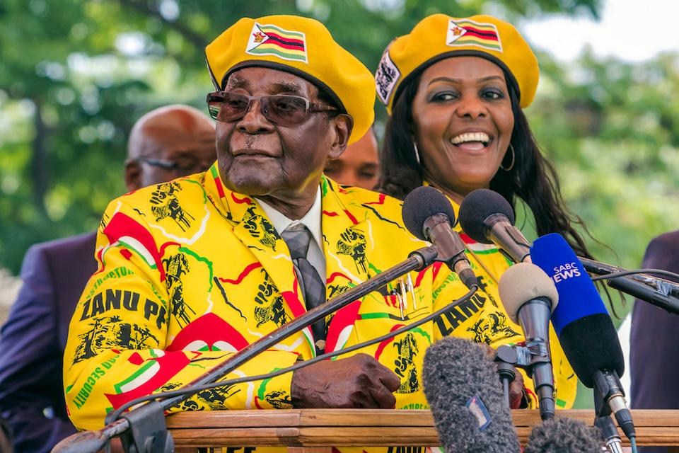 Zimbabwe's President Robert Mugabe (L) addresses party members and supporters gathered at his party headquarters to show support to Grace Mugabe (R) becoming the party's next vice president after the dismissal of Emerson Mnangagwa November 8, 2017.