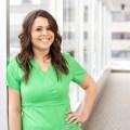 A nurse in green scrubs next to windows