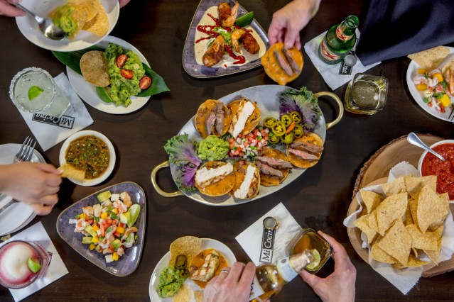 A straight down photograph of peoples hands grabbing food off a table