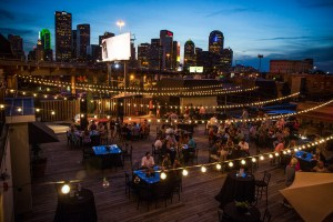 An event on a high rise deck, photography showing the Dallas skyline in the background