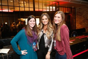 Girls pose with celebrity at a concert in Dallas