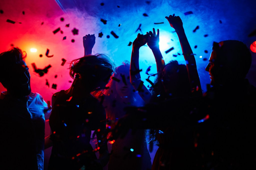 Silhouettes of dancers moving in confetti from a corporate DJ. Dallas audio equipment rental.