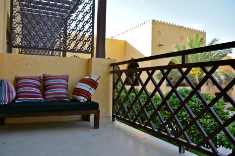 Private balcony of the Al Sahab room overlooking the pool and green lawns at Tilal Liwa Hotel