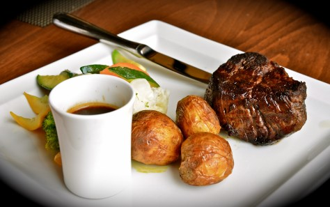 Grilled new zealand beef medallion served with baked potato, steamed vegetable and wild pepper sauce - dhs 130