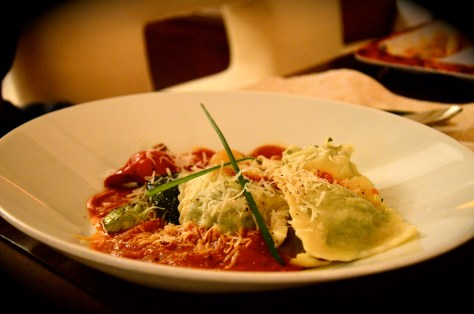 Ravioli Ricotta and Spinach stuffed pasta, on a bed of grilled Mediterranean vegetables and tomato sauce