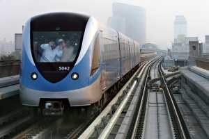 Passengers wave from a passing train on the Dubai Metro network. The Metro completes one month today. Randi Sokoloff / The National