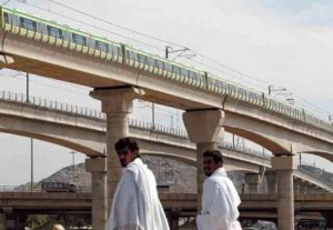 *  A Makkah Metro train passes over pilgrims' heads. The first phase of the Makkah Metro project is transporting pilgrims between the cities of Mina, Arafat and Muzdalifa.     * Image Credit: AP