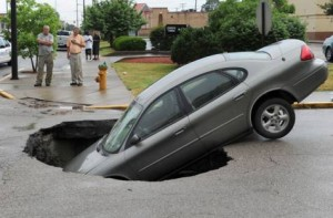 Image Credit: AP A car rests in a hole after a water main broke on Oregon St. at Main St. in Evansville, Ind. on Friday, May 30, 2014. The car's owner, rear left, said he, his girlfriend and two children were in the car at the time.