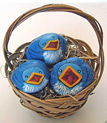Hungry baby blue birds painted on rocks and displayed in a nest basket