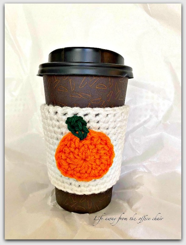 Crocheted pumpkin design cozy for coffee cup