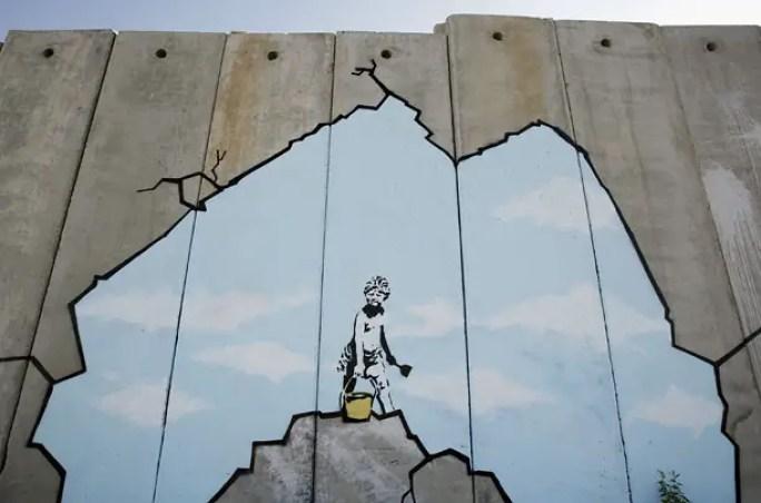Una delle opere realizzate da Banksy sul muro di divisione in Cisgiordania