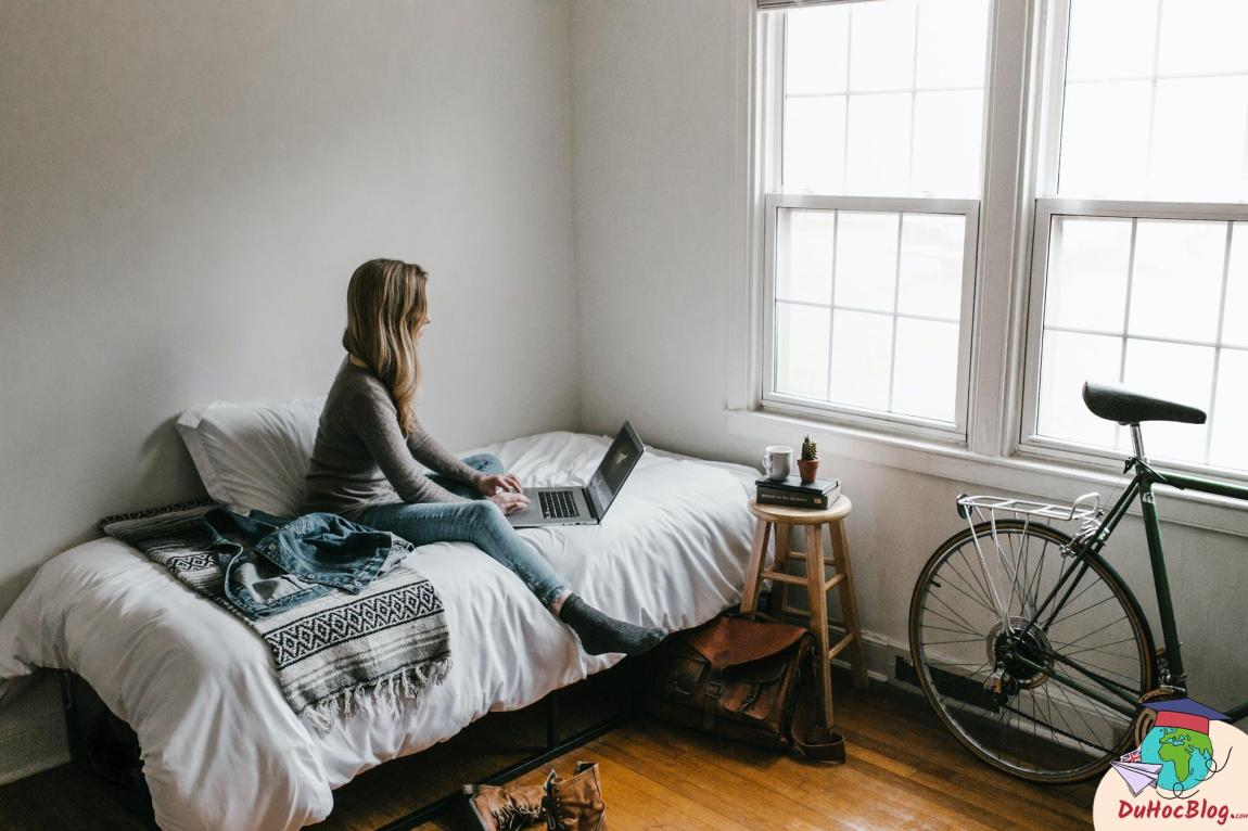 woman in gray shirt sitting on bed