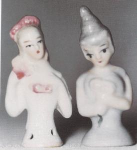 """To små halvdukker fra hver sin Verdensdel: tv en lillebitte en på ca. 4 cm med en vifte i hænderne. Hun har rosa bånd i håret og er mærket """"6241 Germany"""". Også dukken i samme størrelse th med den usædvanlige frisure holder en vifte eller blomster i hænderne. Hun er fremstillet i Japan!"""