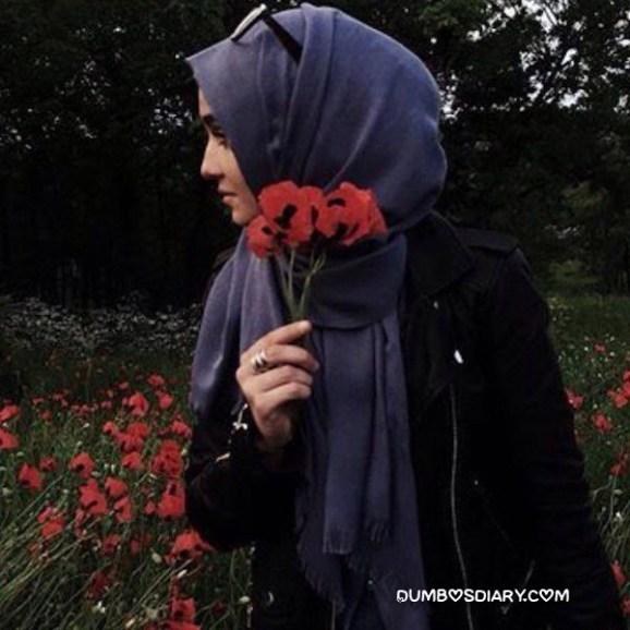 Cute hijabi girl holding red flower standing in garden