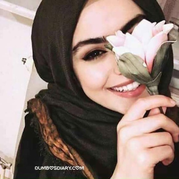 Cute hijabi girl smiling and hidding her face with rose