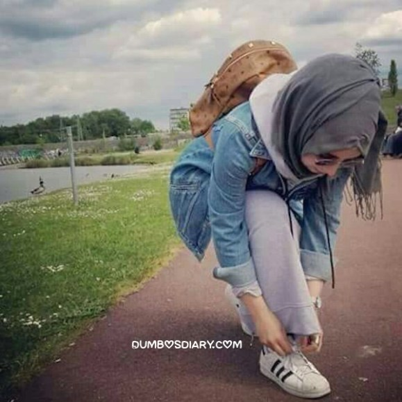 Cute pretty innocent hijabi muslim girl tie up laces of her shoes