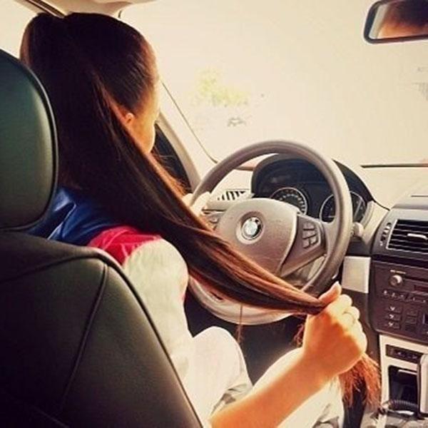 Girl holding her hair in car