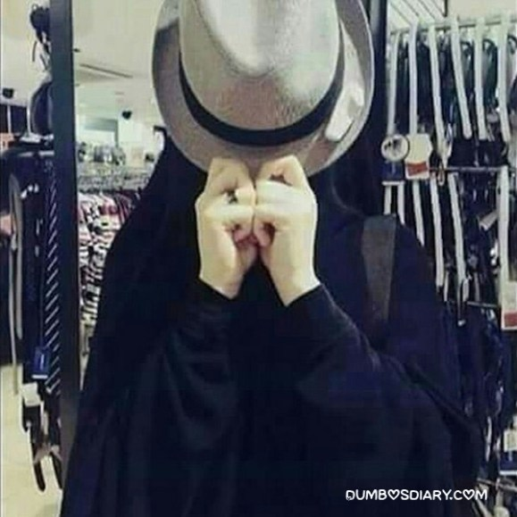 Girl in hijab hidding her face with cow hat