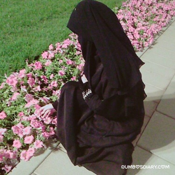 Hidden face hijabi muslim girl plucking up flower