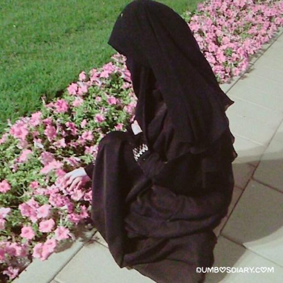 Hidden face hijabi muslim girl plucking up flower