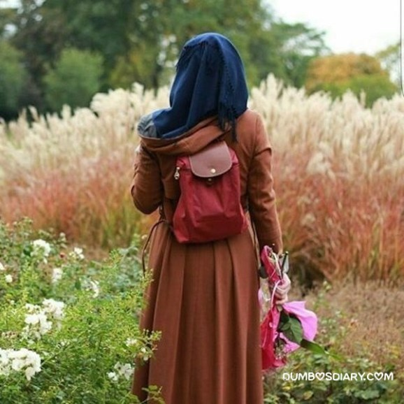 Hidden face innocent hijabi girl standing in beautiful fields