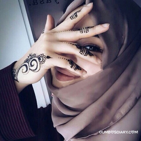 Pretty girl hidding her face with henna hands hijabi muslimah