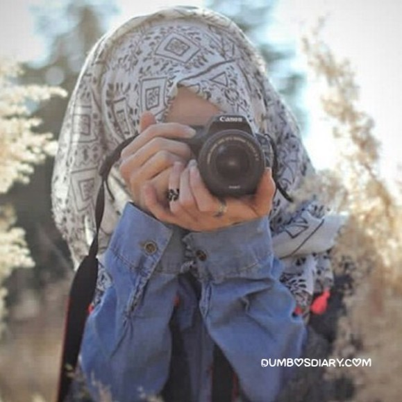 Pretty hijabi girl hid face with dslr