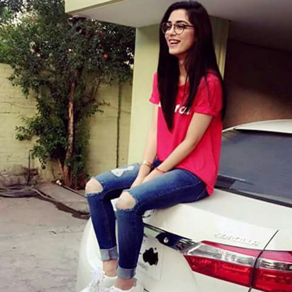 Smiling girl sitting on the car