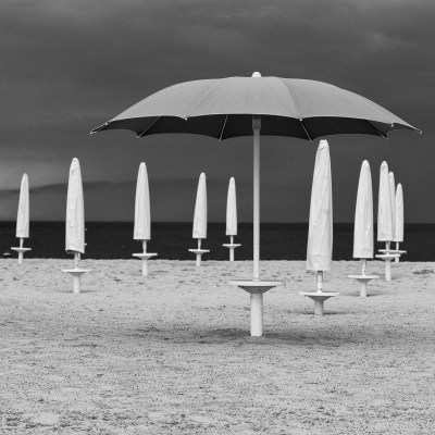 As a storm rolls in from the sea beach umbrellas are packed away. Dubai, UAE