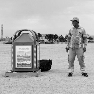 A beach cleaner smokes a cigarette on the beach in Umm Suqeim, Dubai