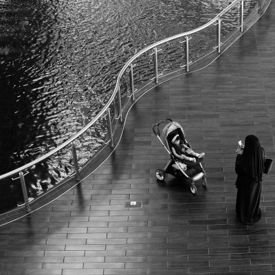 A woman photographing her daughter in front of the fountain in Dubai Mall