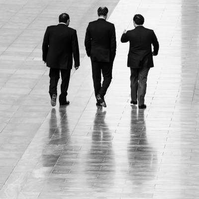 Three businessmen walking in the main precinct of DIFC in Dubai