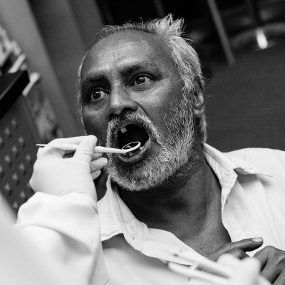 A man with few remaining teeth has a dental checkup as part of a free clinic for labourers in Dubai